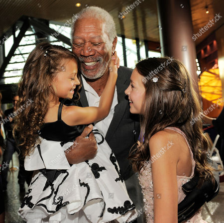 """Morgan Freeman, center, star of """"The Magic of Belle Isle,"""" embraces fellow cast members Nicolette Pierini, left, and Emma Fuhrmann at the premiere for the film at the Director's Guild of America on in Los Angeles"""