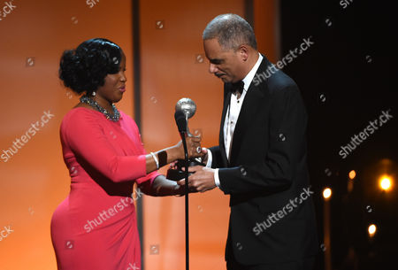 NAACP chairman Roslyn M. Brock, left, presents Attorney General of the United States Eric Holder with the Chairman's Award on stage at the 46th NAACP Image Awards at the Pasadena Civic Auditorium, in Pasadena, Calif