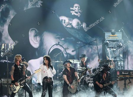 Duff McKagan, left, performs with Alice Cooper, Johnny Depp, and Joe Perry of Hollywood Vampires at the 58th annual Grammy Awards, in Los Angeles. Pictured on screen is Lemmy of Motorhead