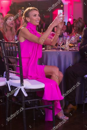 Stock Photo of Giuliana Rancic takes photos of Bill Rancic speaking on stage at The Pink Agenda's annual benefit gala at Three Sixty, in New York