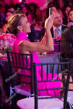 Giuliana Rancic takes photos of Bill Rancic speaking on stage at The Pink Agenda's annual benefit gala at Three Sixty, in New York