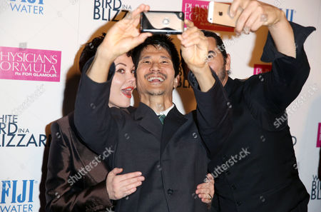 """Rose McGowan, left, Gregg Araki, center, and James Duval take a selfie at the premiere of """"White Bird in a Blizzard"""" presented by FIJI Water on in Los Angeles"""