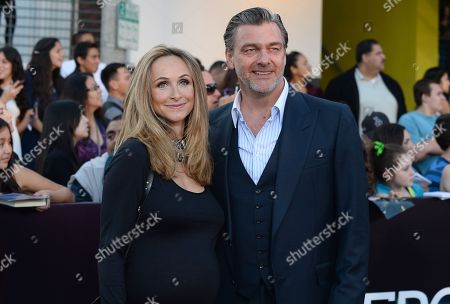 """Elisabetta Caraccia, left, and Ray Stevenson arrive at the world premiere of """"Divergent"""" at the Westwood Regency Village Theater, in Los Angeles"""