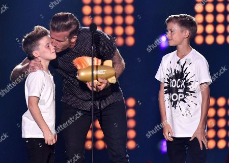 David Beckham, center, with his sons, from right, Romeo James Beckham and Cruz David Beckham, accepts the legend award at the Kids' Choice Sports Awards at UCLA's Pauley Pavilion, in Los Angeles