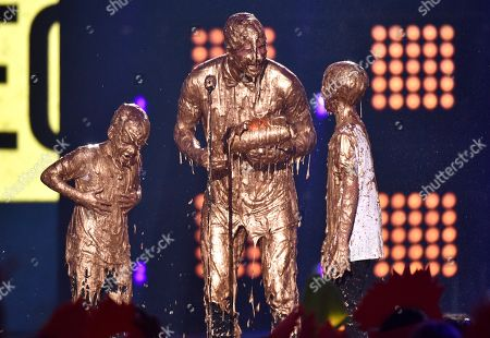 David Beckham, center, with his sons, from right, Romeo James and Cruz David, get slimed as Beckham accepts the legend award for at the Kids' Choice Sports Awards at UCLA's Pauley Pavilion, in Los Angeles
