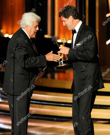 Jay Leno, left, presents the award for outstanding comedy series to Steven Levitan and the producers of Modern Family at the 66th Annual Primetime Emmy Awards at the Nokia Theatre L.A. Live, in Los Angeles