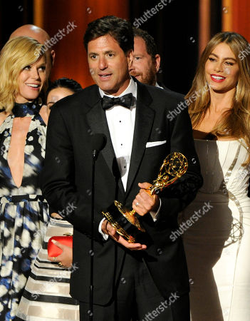 Steven Levitan, center, accepts the award for outstanding comedy series for his work on Modern Family at the 66th Annual Primetime Emmy Awards at the Nokia Theatre L.A. Live, in Los Angeles. Looking on from left are Julie Bowen and Sofía Vergara