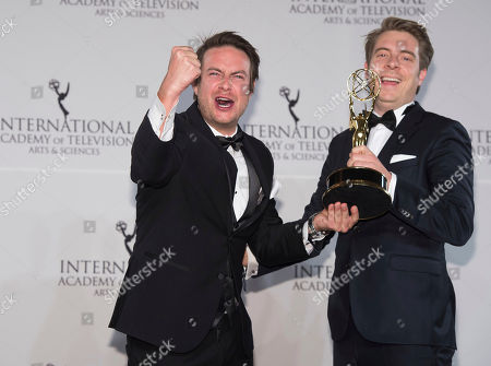 Stock Image of Matthias Bittner, left, and Paul Zischler winners of the Documentary award appear in the press room for the 44th International Emmy Awards at the New York Hilton, in New York