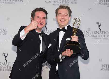 Stock Picture of Matthias Bittner, left, and Paul Zischler winners of the Documentary award appear in the press room for the 44th International Emmy Awards at the New York Hilton, in New York