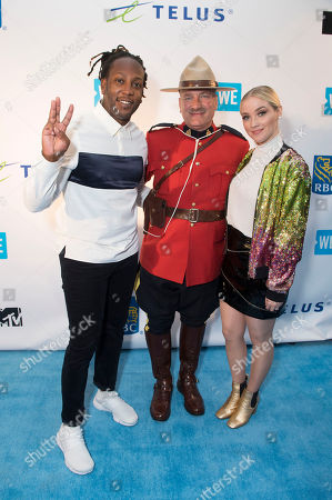 Stock Picture of From left, Tyrone Edwards, RCMP Constable Terry Russel and Liz Trinnear arrive at WE Day, in Toronto