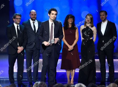 """Director Damien Chazelle, center, accepts the award for best picture for """"La La Land"""" at the 22nd annual Critics' Choice Awards at the Barker Hangar, in Santa Monica, Calif. Pictured on stage from left, Gary Gilbert, Jordan Horowitz, Mary Zophres, Emma Stone, and Ryan Gosling"""