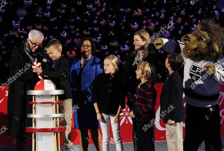 Fritz Coleman, left, and Johnny Hoffman, Junior Ambassador for Children's Hospital Los Angeles, pull the lever to the light the Holiday Tree as Los Angeles councilwoman Jan Perry, third from left, looks on at the 5th annual Holiday Tree Lighting at L.A. Live and opening of LA Kings Holiday Ice, in Los Angeles