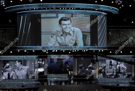 """Ron Howard presents an """"In Memorial"""" at the 64th Primetime Emmy Awards at the Nokia Theatre, in Los Angeles. Pictured onscreen is Andy Griffith"""