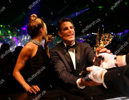 """Stock Picture of Lee Metzger, right, poses with the award for outstanding reality-competition program for """"the Voice,"""" and guest attend the Governors Ball for the 68th Primetime Emmy Awards at the Los Angeles Convention Center, in Los Angeles"""