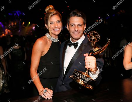 """Stock Image of Lee Metzger, right, poses with the award for outstanding reality-competition program for """"the Voice,"""" and guest attend the Governors Ball for the 68th Primetime Emmy Awards at the Los Angeles Convention Center, in Los Angeles"""