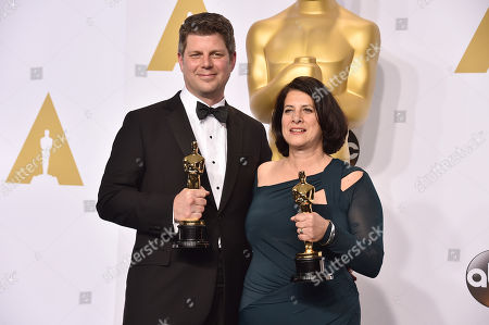 Adam Stockhausen, left, and Anna Pinnock pose in the press room with the award for best production design for their work on The Grand Budapest Hotel at the Oscars, at the Dolby Theatre in Los Angeles