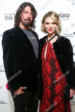Dave Grohl, left, and wife Jordyn Blum arrive at the 2016 Elton John AIDS Foundation Oscar Viewing Party at West Hollywood Park, in West Hollywood, Calif