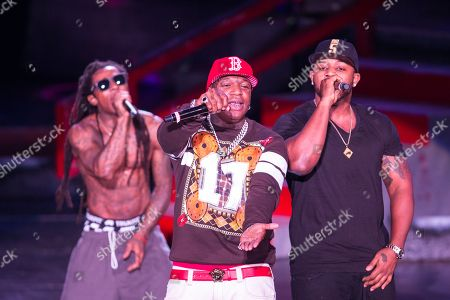 From left, Lil Wayne (AKA Dwayne Michael Carter, Jr.), Birdman (AKA Bryan Williams) and Mack Maine (AKA Jermaine Preyan) perform as a part of the America's Most Wanted Tour at the Verizon Wireless Amphitheater on in Irvine, Calif