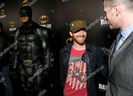 Stock Photo of Seth Green, left, and Allan Heinberg, writer of Batman Live pose with Batman at the L.A. Batman Live Premiere, at STAPLES Center in Los Angeles