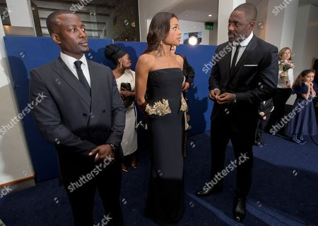 South African actor Tony Kgoroge looks, left, as British actors Idris Elba, right, and Naomie Harris chat ahead of the UK Premiere of the Long Walk to Freedom, a film based on the South African President Nelson Mandela's autobiography of the same name, to the Odeon cinema in Leicester Square, central London