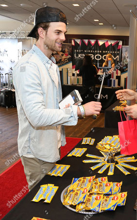 Actor Nathaniel Buzolic, left, samples Butterfinger Cups, as Butterfinger butts into awards season at Kari Feinstein's Oscars Style Lounge on in West Hollywood, Calif. Fans can see more of the Butterfinger Commentators at ButterfingerCups.com