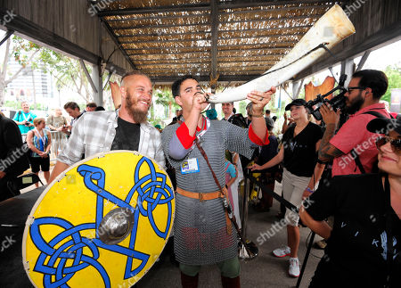"""IMAGE DISTRIBUTED FOR CIVIC ENTERTAINMENT GROUP - Travis Fimmel of HISTORY's """"Vikings"""", left, looks on as fan Michael Howell blows a horn at All Hail Vikings: An Interactive Experience outside the 2013 Comic-Con International Convention on in San Diego. Throughout the weekend, fans competed in longboat races in a custom 50-foot waterway, met with cast members and received a limited edition comic book written by series creator Michael Hirst"""