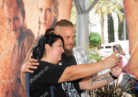 """Travis Fimmel of HISTORY's """"Vikings"""", left, poses with a fan at All Hail Vikings: An Interactive Experience outside the 2013 Comic-Con International Convention on in San Diego. Throughout the weekend, fans competed in longboat races in a custom 50-foot waterway, met with cast members and received a limited edition comic book written by series creator Michael Hirst"""