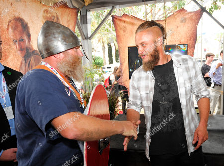 """Travis Fimmel of HISTORY's """"Vikings"""", right, shakes hands with a fan at All Hail Vikings: An Interactive Experience outside the 2013 Comic-Con International Convention on in San Diego. Throughout the weekend, fans competed in longboat races in a custom 50-foot waterway, met with cast members and received a limited edition comic book written by series creator Michael Hirst"""
