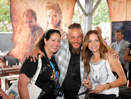 """Travis Fimmel, center, and Jessalyn Gilsig, right, pose with a fan of HISTORY's """"Vikings"""" at All Hail Vikings: An Interactive Experience outside the 2013 Comic-Con International Convention on in San Diego. Throughout the weekend, fans competed in longboat races in a custom 50-foot waterway, met with cast members and received a limited edition comic book written by series creator Michael Hirst"""