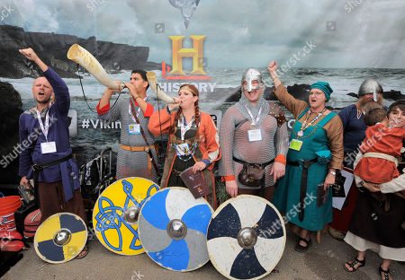 """Fans dressed as Vikings pose for photos at HISTORY's """"Vikings"""" signs shield as prizes for fans at All Hail Vikings: An Interactive Experience outside the 2013 Comic-Con International Convention on in San Diego. Throughout the weekend, fans competed in longboat races in a custom 50-foot waterway, met with cast members and received a limited edition comic book written by series creator Michael Hirst"""