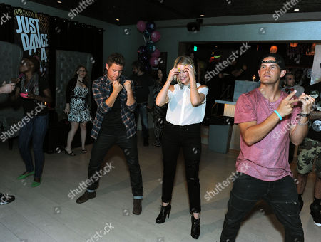 """The Bachelorette"""" winner Jef Holm, left, dances to Ubisoft's Just Dance 4 with party host Ashley Benson, center, and Cody Barker at the launch party on in Los Angeles.Just Dance 4 hits store shelves on Tuesday, Oct. 9, 2012"""