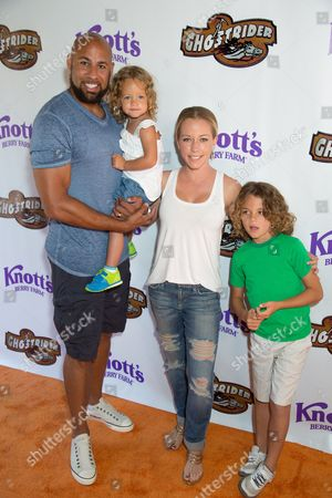 Hank Baskett, from left, Alijah Baskett, Kendra Wilkinson and Hank Baskett Jr. arrive at the event to celebrate the return of the Ghostrider at Knott's Berry Farm, in Buena Park, Calif