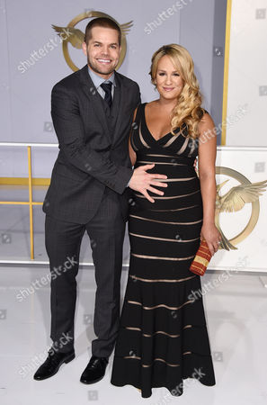 """Wes Chatham, left, and Jenn Brown arrive at the Los Angeles premiere of """"The Hunger Games: Mockingjay - Part 1"""" at the Nokia Theatre L.A. Live on"""