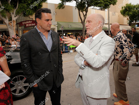 """Producer Mark Vahradian (L) and actor John Malkovich arrive on the red carpet at the LA premiere of """"Red 2"""" at the Westwood Village on in Los Angeles"""