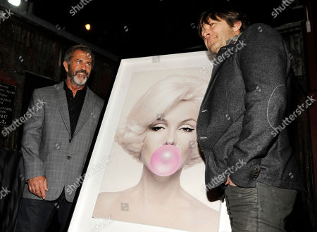 """Actor/filmmaker Mel Gibson, left, poses with artist Moebius and one of his works at the Mending Kids """"Rock N' Roll All Star Event"""", in West Hollywood, Calif"""