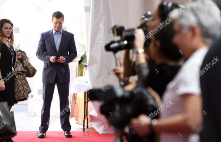 """Peter Krause, a cast member in the television series """"Parenthood,"""" checks his phone as he waits for fellow cast member Monica Potter to walk the red carpet at the NBC 2015 Winter TCA Press Tour at The Langham Huntington Hotel, in Pasadena, Calif"""