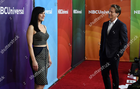 """Kyra Zagorsky, left, a cast member in the Syfy series """"Helix,"""" poses for photographers as fellow cast member Steven Weber looks on at the NBCUniversal Cable 2015 Winter TCA Press Tour at The Langham Huntington Hotel, in Pasadena, Calif"""
