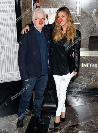 Comic Relief Chief Executive, Kevin Cahill, left, and singer Nicole Scherzinger light the Empire State Building in honor of NBC's Red Nose Day entertainment charity event, in New York