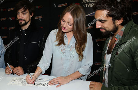 """Blake Ritson, left, Laura Haddock, center, and Gregg Chillin, from the STARZ television show """"Da Vinci's Demons"""", sign autographs during New York Comic Con on in New York"""