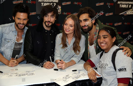 """From left, Tom Riley, Blake Ritson, Laura Haddock, and Gregg Chillin, from the STARZ television show """"Da Vinci's Demons"""", take a picture with a fan while signing autographs during New York Comic Con on in New York"""