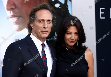 """William Fichtner, left, and Kymberly Kalil arrive at the world premiere of """"Elysium"""" at the Regency Village Theater on in Los Angeles"""
