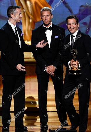 "SEPTEMBER 15: (L-R) Dan Savage and Terry Miller accept the Governors Award for ""It Gets Better Project"" from presenter Academy Chairman & CEO Bruce Rosenblum onstage at the Academy of Television Arts & Sciences 64th Primetime Creative Arts Emmy Awards at Nokia Theatre L.A. Live on in Los Angeles, California"