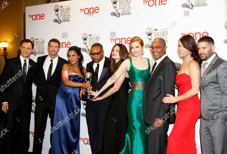 The cast of Scandal, from left, Tony Goldwyn, Scott Foley, Kerry Washington, Columbus Short, Katie Lowes, Darby Stanchfield, Joe Morton, Bellamy Young, and Guillermo Diaz pose in the press room with the award for outstanding drama series at the 45th NAACP Image Awards at the Pasadena Civic Auditorium, in Pasadena, Calif