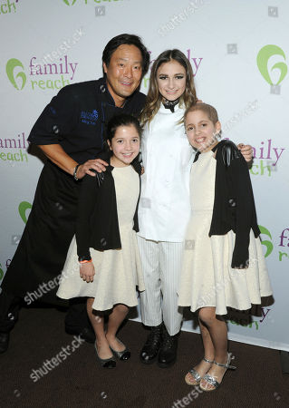 Chef Ming Tsai, left, Family Reach National Advisory Board President, and singer Daya, second right, pose with twins Sabrina and Olivia Lorusso at Family Reach's Cooking Live! charity event, at The Ritz-Carlton New York, Battery Park. The event raises funds to help families facing the daily cost of cancer