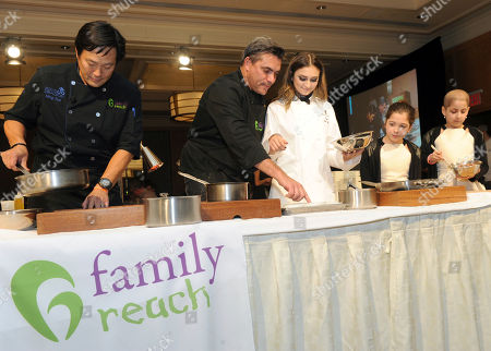 Chef Ming Tsai, chef Todd English, singer Daya and twins Sabrina and Olivia Lorusso, left to right, prepare a dish at Family Reach's Cooking Live! charity event, at The Ritz-Carlton New York, Battery Park. The event raises funds to help families facing the daily cost of cancer