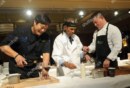Veteran broadcaster Bryant Gumbel, center, prepares a dish with chef Ming Tsai, left, and chef Shaun Hergatt at Family Reach's Cooking Live! charity event, at The Ritz-Carlton New York, Battery Park. The event raises funds to help families facing the daily cost of cancer