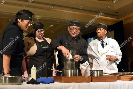 Iron Chef Morimoto, second right, and veteran broadcaster Bryant Gumbel, right, with chef Ming Tsai, left, and guest Christine Rogers, prepare a dish at Family Reach's Cooking Live! charity event, at The Ritz-Carlton New York, Battery Park. The event raises funds to help families facing the daily cost of cancer