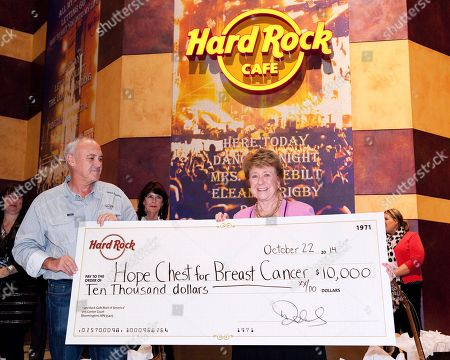 Hamish Dodds, President and CEO of Hard Rock International, presents a donation to Barbara Hensley, founder of the local charity Hope Chest for Breast Cancer at the Grand Opening of Hard Rock Cafe Mall of America, in Bloomington, Minn