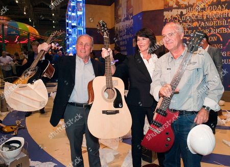 Bloomington Mayor Gene Winstead, President and CEO of the Bloomington Convention and Visitors Bureau Bonnie Carlson and President and CEO of Hard Rock International Hamish Dodds hold up pieces of broken, defective guitars they smashed to commemorate the Grand Opening of Hard Rock Cafe Mall of America, in Bloomington, Minn