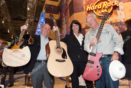 Stock Picture of Bloomington Mayor Gene Winstead, President and CEO of the Bloomington Convention and Visitors Bureau Bonnie Carlson and President and CEO of Hard Rock International Hamish Dodds hold up pieces of broken, defective guitars they smashed to commemorate the Grand Opening of Hard Rock Cafe Mall of America, in Bloomington, Minn